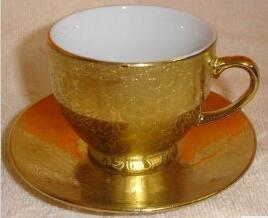 Golden ceramic coffee cup and saucer